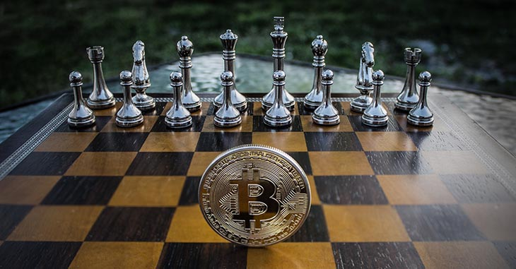 Picture of chess board with Bitcoin token to accompany article about Kasparov's opinions on cryptocurrency
